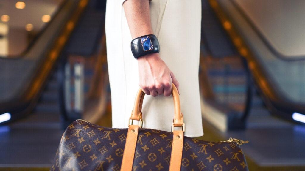 Woman holding Louis Vuitton purse