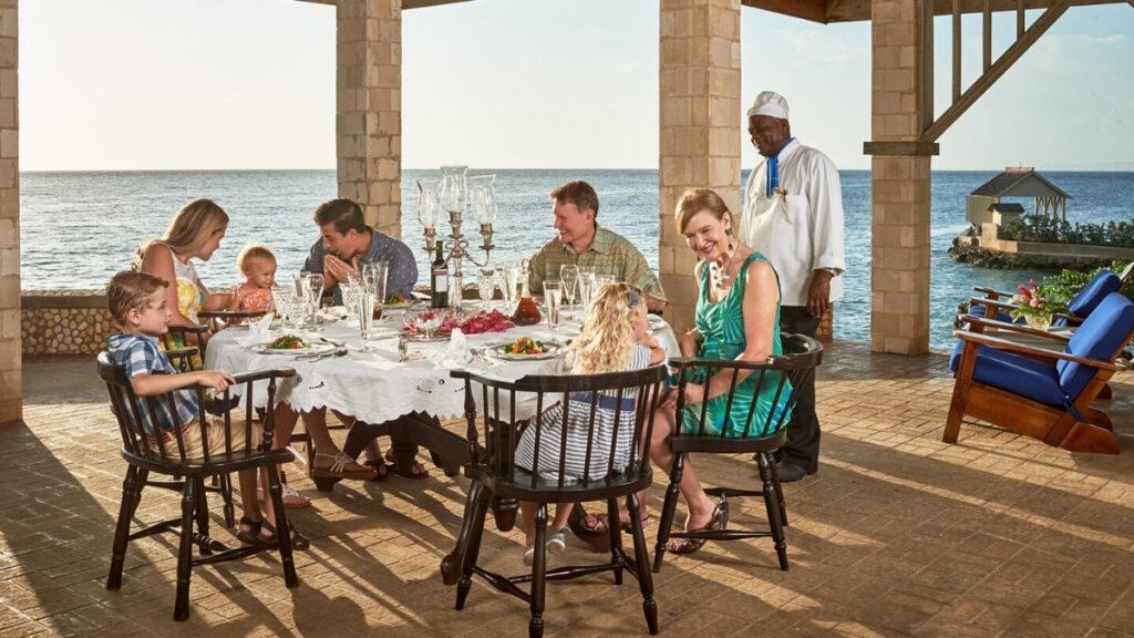 Family having dinner in their luxury villa in Jamaica